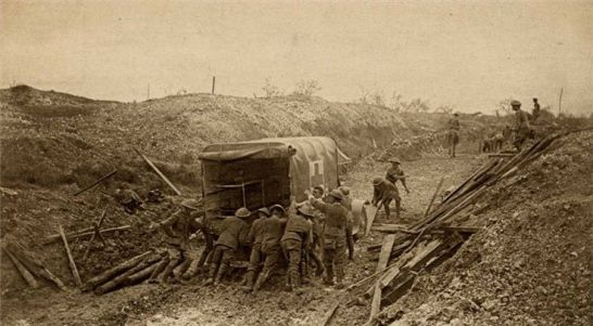 Ambulance workers pushing a truck out of the mud c.1915.